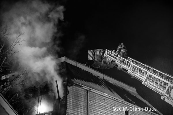 firefighters in tower ladder platform at fire