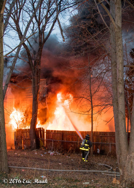 flames engulf the rear of a house