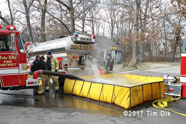 fire department water tanker dumping into portable tank