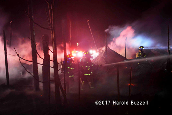 firefighters battle barn fire at night