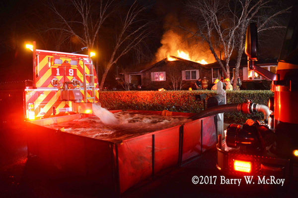 fire department water tender dumps into portable tank with house on fire