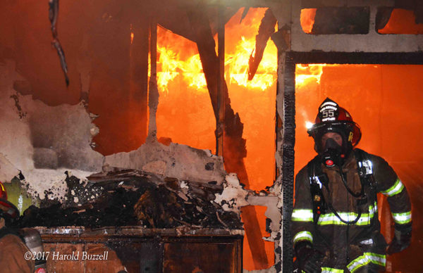 firefighter with PPE exiting burning building