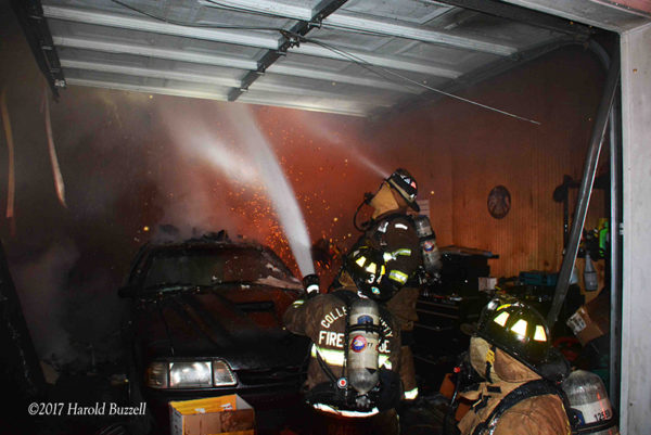 firefighters with hose line in garage