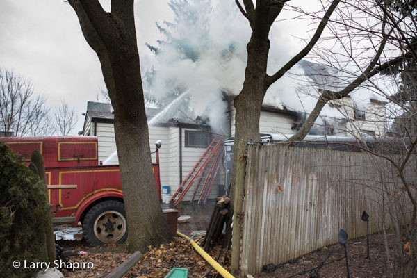 antique fire truck in driveway of house on fire