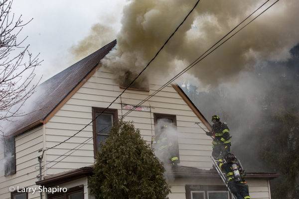 heavy smoke from attic of house on fire