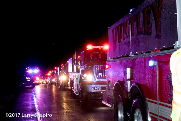 many fire department water tenders in line at a fire scene