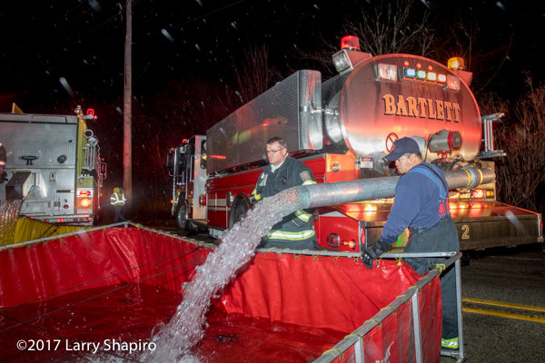 Bartlett fire department tenet dumps water into a portable tank