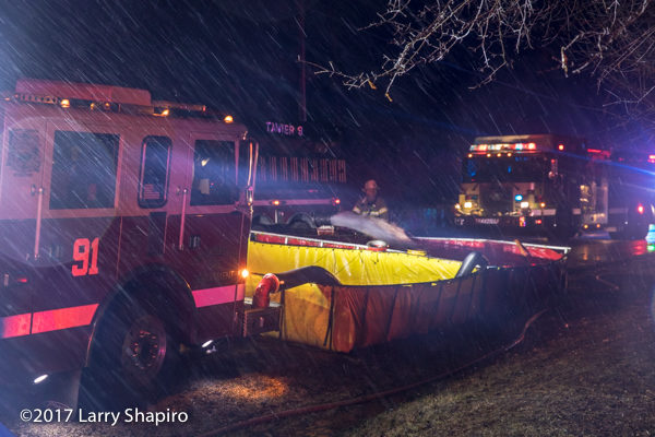 fire department tenet dumps water into a portable tank