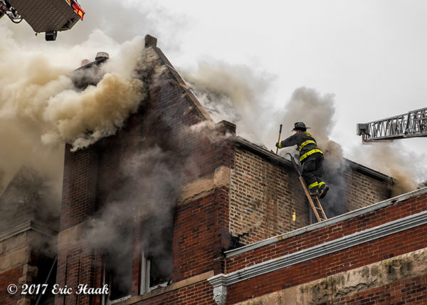 Firefighter on roof with heavy smoke