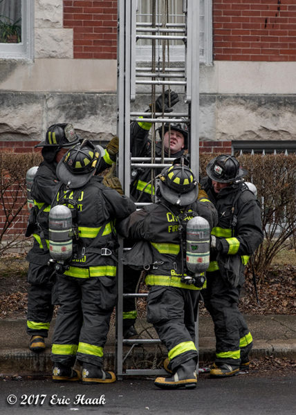 Firefighters raise large ground ladder
