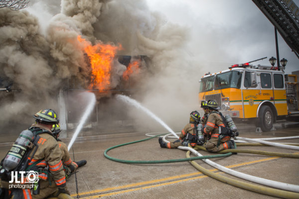 firefighters battle fire with heavy smoke and flames