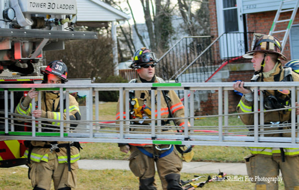 firefighters carry ground ladder