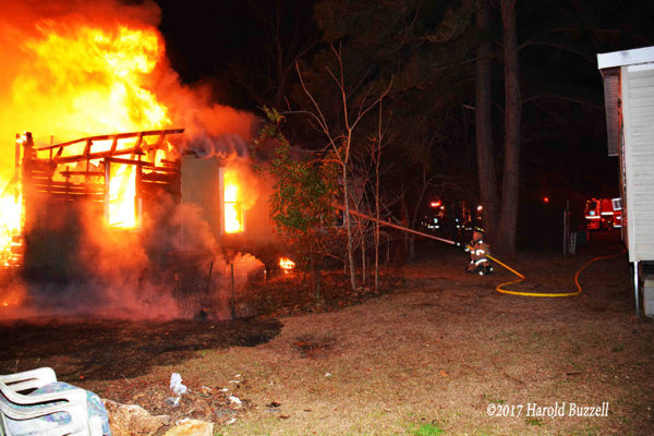firefighter battles rural house fire at night