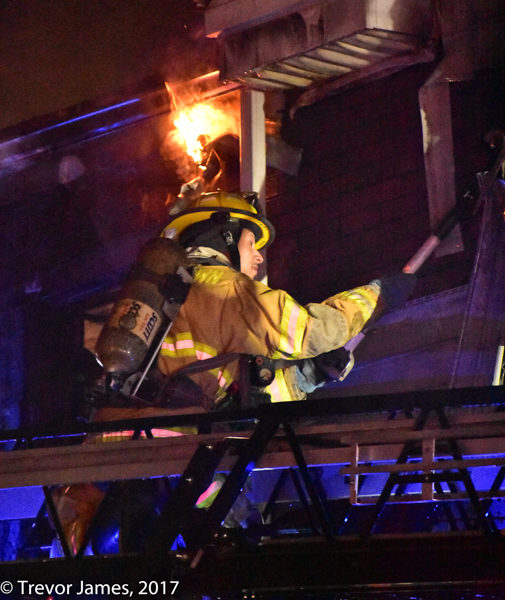 firefighter on aerial ladder at night
