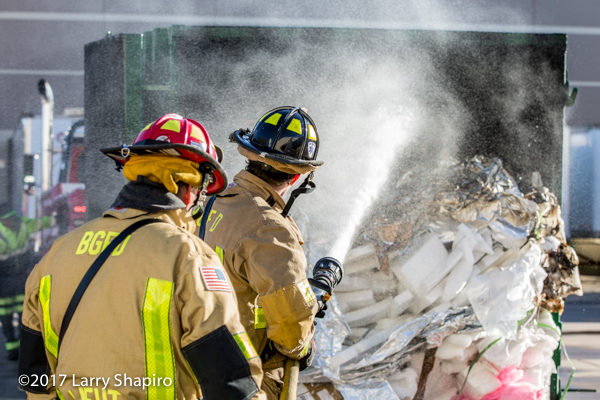 Firefighters soak contents of dumpster after a fire