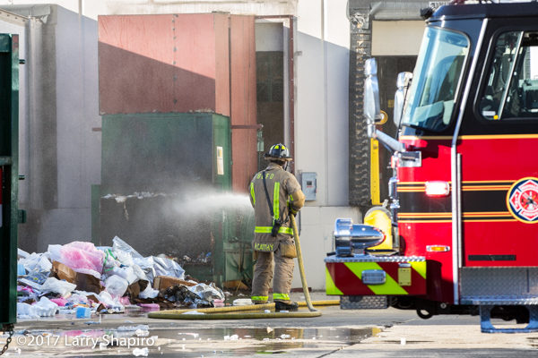 Firefighter soaks contents of dumpster after a fire