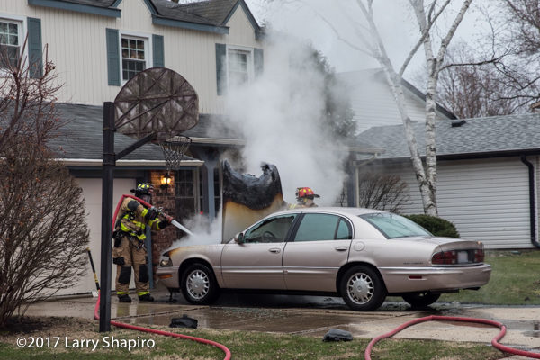 Firefighters extinguish a car fire