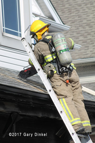 firefighter vents roof with saw from ladder