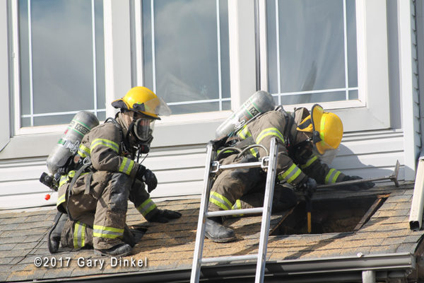 firefighter with PPE inspects roof vent hole