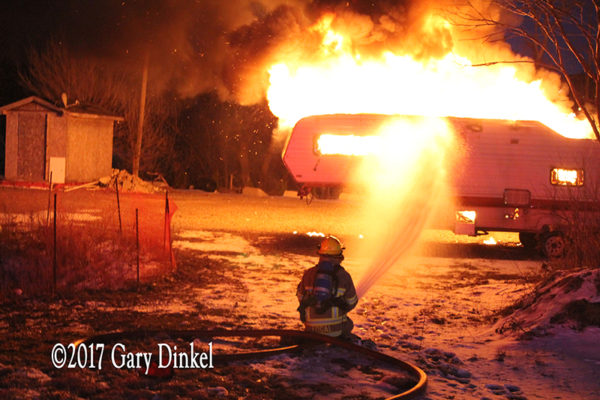 firefighter battles a recreational trailer engulfed in fire
