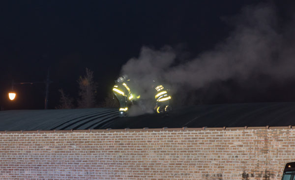 Firefighters on truss roof with smoke