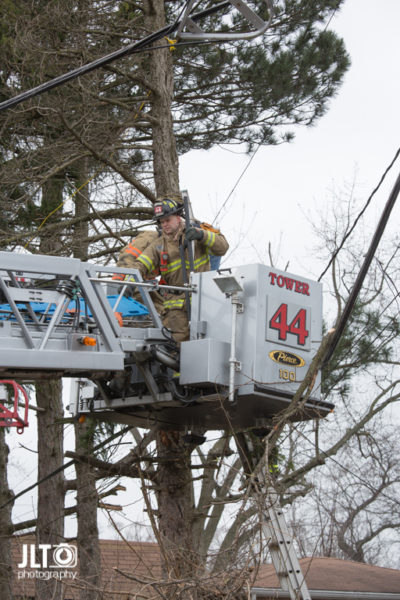 firefighters remove patient in tower ladder platform
