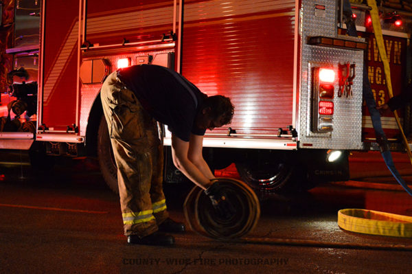 firefighter rolls hose after a fire