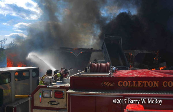 firefighter operates deck gun at fire scene