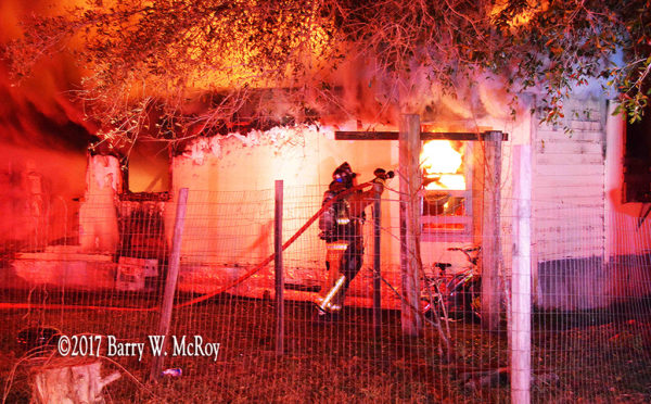 firefighter battles fire at rural house at night