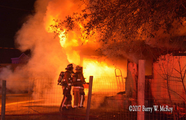 firefighters approach as fire engulfs rural house at night
