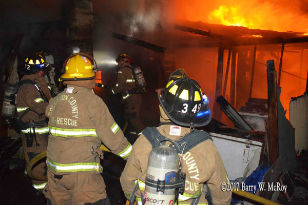 firefighters with hose battle fire