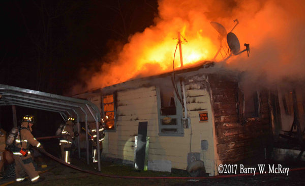 heavy flames through roof of rural house at night