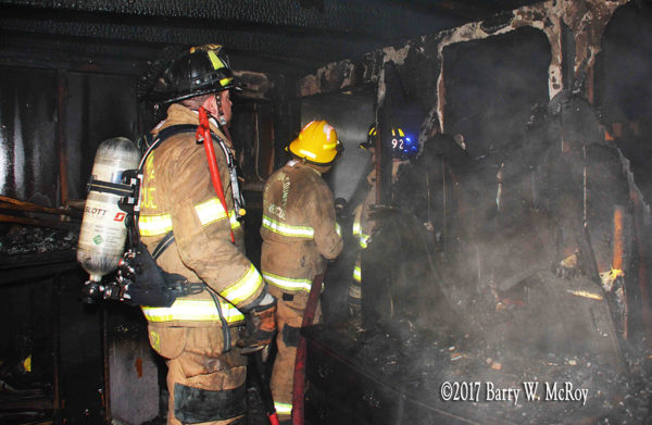 firefighters with hose inside burned out house