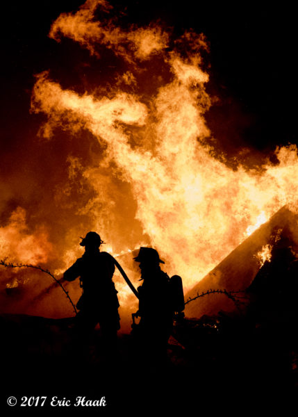 silhouette of firefighters with massive inferno