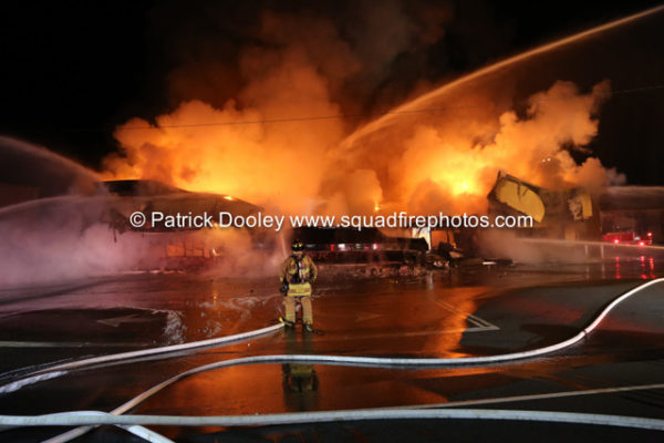 firefighters battle fire that destroyed a commercial business at night