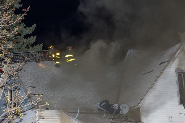 firefighters vent roof at night with heavy smoke