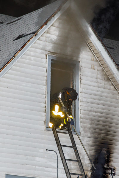 firefighter leans out window with heavy smoke
