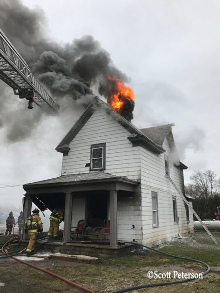 flames burn through roof of a house