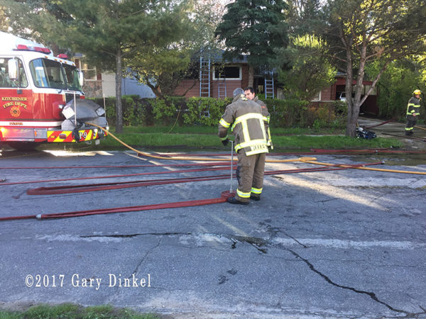 firefighter rolls hose after fire