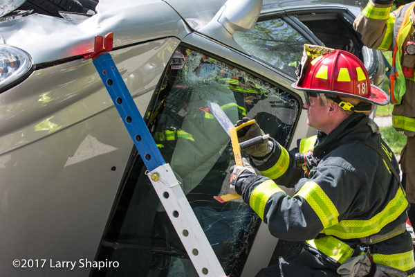 Firefighter cuts windshield at crash scene