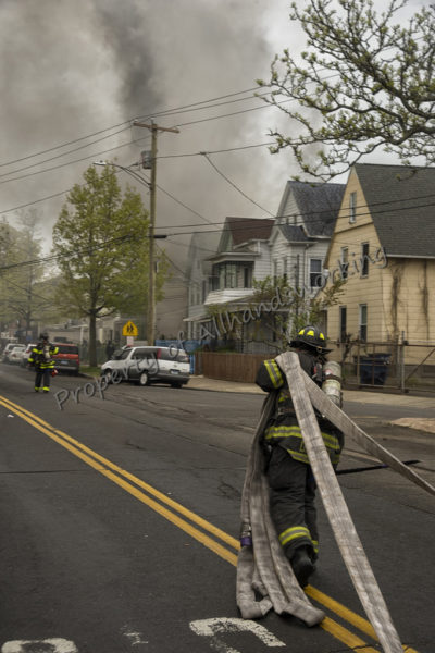firefighter pulling hose in street