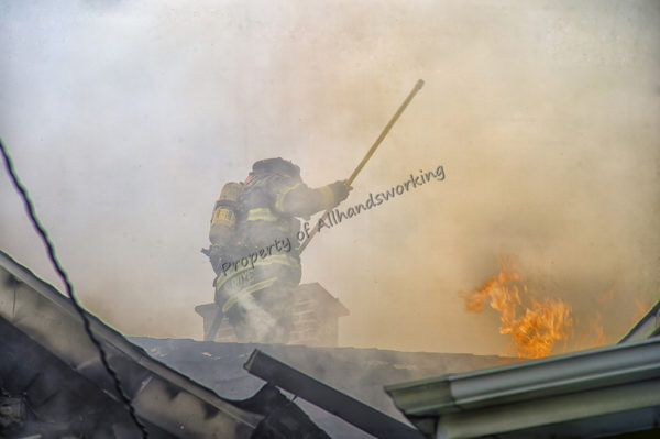 firefighter on roof with flames