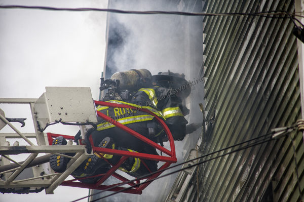 firefighter on aerial ladder tip at fire