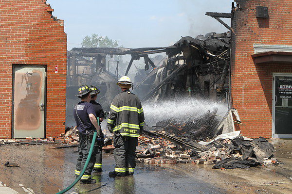 firefighters hitting hit spots with hose