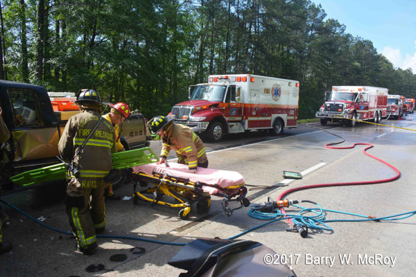 firefighter/paramedics with Stryker cot at crash site