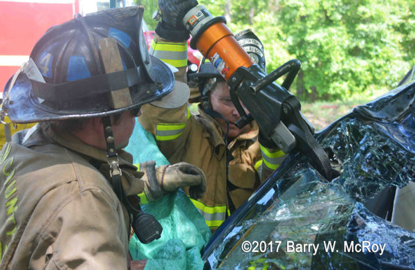 firefighters use Holmatro cutters at a crash site
