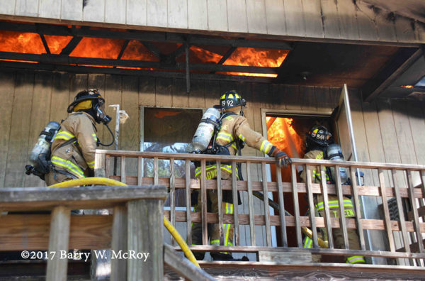firefighters advance a hose line against heavy fire