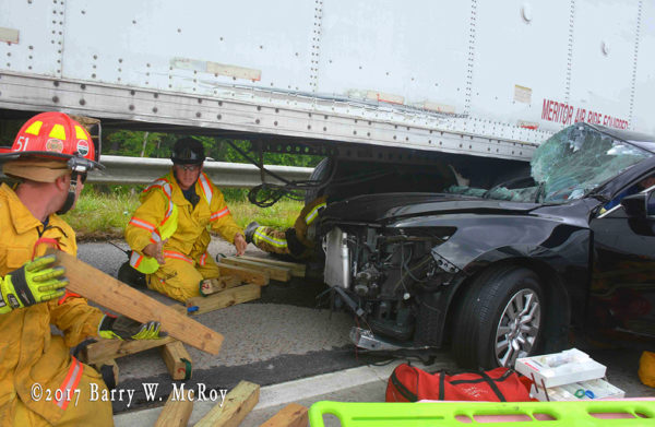 firefighters use cribbing to lift trailer from car