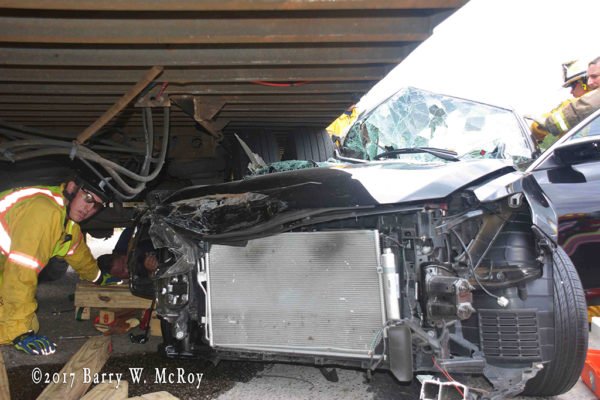 car wedged under semi trailer after crash