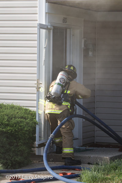 Firefighter makes entry with hose